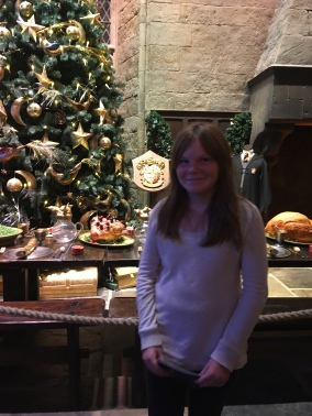 Samantha standing by her Gryffindor table